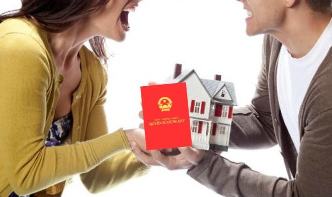 2 vợ chồng cùng cầm trên tay mô hình ngôi nhà và cuốn sổ đỏ nhà đất
