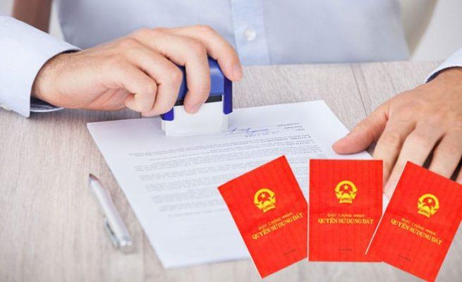 một người đang đóng dấu vào tờ hợp đồng, bên cạnh là hình ảnh các cuốn sổ đỏ